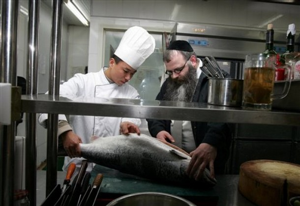 Rabbi Shimon Freundlich, right, checks a fish with chef Xiao Wei in the kitchen at Dini's Kosher Restaurant in Beijing, Tuesday Jan. 29, 2008. Rabbi Freundlich, the religious leader of Beijing's Jewish community, is likely to be instrumental in running the Kosher kitchen at the Athletes Village during this summer's Beijing Olympics. (AP Photo/Greg Baker)